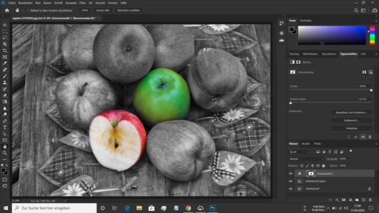 Teilkoloriertes Schwarz Weiss Bild mit einem grünen und einem aufgeschnittenen roten Apfel als Eye Catcher