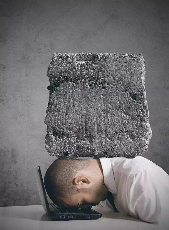 Symbolische Darstellung einer kreativen Blockade: Ein großer Stein drückt einen Kopf auf einen Laptop